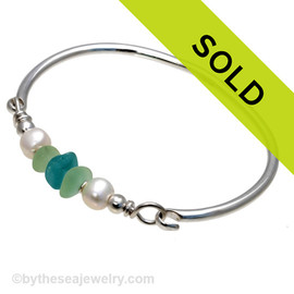Three pieces of beach found sea glass in a a thick vivid aqua and two vivid seafoam green on this solid sterling silver full round sea glass bangle bracelet. Sorry this sea glass jewelry selection has been sold!