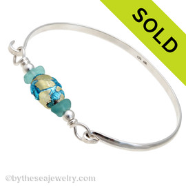 Two pieces of vivid tropical aqua sea glass set on a half round bangle with a vintage handmade center bead. SOLD - Sorry this Sea Glass Bangle Bracelet is NO LONGER AVAILABLE!