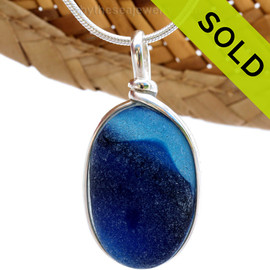 This ultra rare Seaham blue sea glass multi color pendant is set in our Original  Wire Bezel© pendant setting. The accidental mixture of colors almost resembles a sea scene.