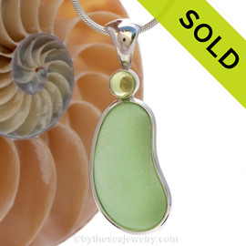 """This beautiful Bright Vivid Seafoam Green sea glass pendant is set in our Deluxe Wire Bezel© pendant setting with a genuine Peridot gem.  A genuine domed genuine peridot 6MM gem is set in a """"tube bezel"""" setting. This is NOT a glued setting but painstakingly burnished to enclose the gem."""