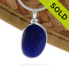 A medium size piece of deep midnight cobalt blue sea glass set in our Original Deluxe Wire Bezel© necklace pendant. This original By The Sea Jewelry setting that encases the glass in silver and leaves both front and back open so you can feel the texture of this antique top quality glass.
