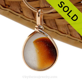 A vivid mixed gold or topaz sea glass pendant set in 14K Rolled Gold Bezel