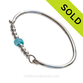 Stunning Vivid Aqua beach found sea glass on this solid sterling silver full round sea glass bangle bracelet. The sea glass is beach found and tumbled only by tide and time found on the beach in England.  SOLD - Sorry this Sea Glass Bangle Bracelet is NO LONGER AVAILABLE!