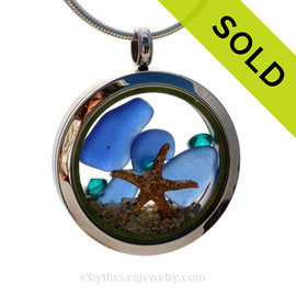 A beautiful pieces of natural blue sea glass combined in a stainless steel locket necklace with a real starfish and beach sand. Tropical aqua crystal gems are added for a bit of beachy bling!