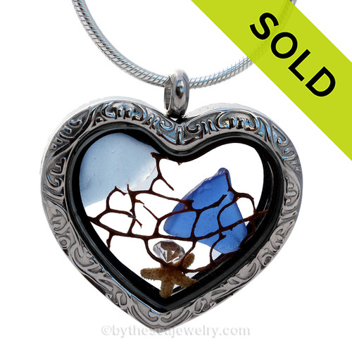 Cobalt Blue and Carolina Blue sea glass combined a silver heart locket necklace with starfish, sea fan and CZ gemstone. This is a reversible locket that has a filigree pattern on one side and is plain on the other side. SOLD - Sorry This Sea Glass Jewelry Selection Is NO LONGER AVAILABLE!