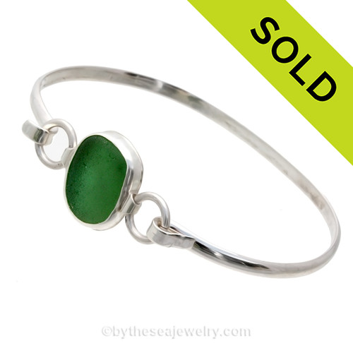 A beach found piece of Deep Sea Green in a Sea Glass Bangle Bracelet set in Fine and Sterling Silver. A detail of this classic set bracelet shows you the tube setting on the side where rings are attached making this a more flexible bracelet than if the rings were attached directly to the sea glass piece. SOLD - Sorry this Sea Glass Bangle Bracelet is NO LONGER AVAILABLE!