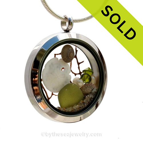 Genuine Seaweed Green sea glass pieces combined with a real baby sandollar, tiny nautilus shells, vintage seafan and genuine freshwater pearl sand real beach sand in this stainless steel locket. SOLD - Sorry this Sea Glass Locket is NO LONGER AVAILABLE!