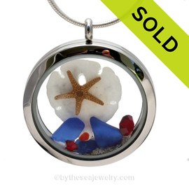 A beautiful sliver of natural blue sea glass combined in a stainless steel locket necklace a real starfish and Baby Sandollar . Vivid Ruby Gems complete the beachy look.