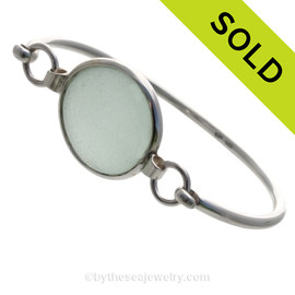 This setting leaves the sea glass piece TOTALLY UNALTERED from the way it was found on the beach. Set in a minimal solid sterling bezel that leaves both front and back open so light can pass through the sea glass piece for maximum color.  SOLD - Sorry this Sea Glass Bangle Bracelet is NO LONGER AVAILABLE!