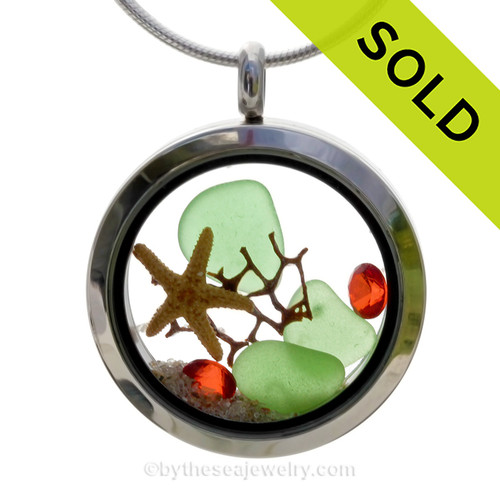 Green sea glass and a real starfish, a bit of vintage sea fan and beach sand make this a great locket necklace for the holidays. Ruby Red  crystal gems finish the locket with some extra bling.