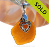 A  perfect amber honey brown genuine sea glass with a solid sterling bail and detailed heart in heart charm. This piece comes complete with our sterling 1.2 MM snake chain.