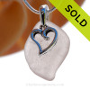 A  perfect pale ridged purple genuine sea glass with a solid sterling bail and detailed swirly heart charm.