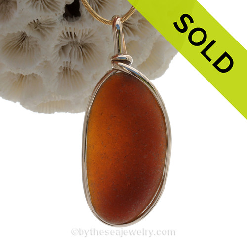 A frosty amber chocolate brown sea glass piece set in our signature 14K Rolled Gold Original Wire Bezel© setting. The sea glass piece is UNALTERED from the way it was found on the beach.! Great warm color for fall and winter!