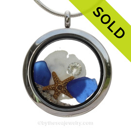 Cobalt Blue Sea Glass in a crystal and stainless steel locket combined with a two baby starfish and vivid White Crystal Gem. Finished with real beach sand for your personal beach on the go!