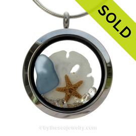 Carolina Blue Sea Glass in a crystal and stainless steel locket combined with a baby starfish, a small sandollar  and vivid White Crystal Gems. Finished with real beach sand for your personal beach on the go! SOLD - Sorry This Sea Glass Locket is NO LONGER AVAILABLE!