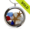 Cobalt Blue and a small piece of Ruby Red Sea Glass in a crystal and stainless steel locket combined with two  baby starfish, sandollar and crystal gems.   SOLD - Sorry This Sea Glass Jewelry Item is NO LONGER AVAILABLE!
