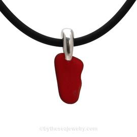 Rare Mini Ruby Red sea glass pendant on a black neoprene cord.
