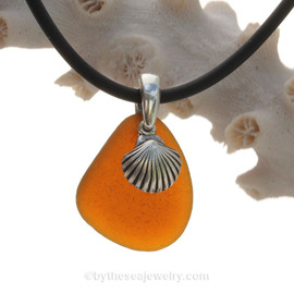 A nice piece of Amber Natural Sea Glass Necklace Set On Silver Bail With Black Neoprene Cord with sterling clasps and finished with a solid sterling Sea Shell Charm.