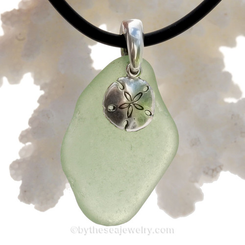 A nice piece of Light Peridot Green Natural Sea Glass Necklace Set On Silver Bail With Black Neoprene Cord with sterling clasps and finished with a solid sterling Sandollar Charm.