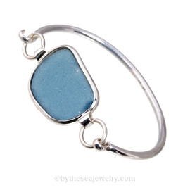 A lovely oblong piece of Stormy Gray Blue Flat Sea Glass Bangle Bracelet set in our Deluxe Wire Bezel© Sterling Silver Setting.  This setting leaves the sea glass piece TOTALLY UNALTERED from the way it was found on the beach. Set in a minimal solid heavy sterling bezel that leaves both front and back open so light can pass through the sea glass piece for maximum color.