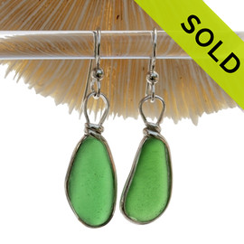 Genuine Natural Oval Pieces of Green Sea Glass in a Sterling Silver Earring set in our Original Wire Bezel© Setting. This setting leaves the glass UNALTERED from the way it was found on the beach. This pair is set in Solid Sterling Silver and will last a lifetime.
