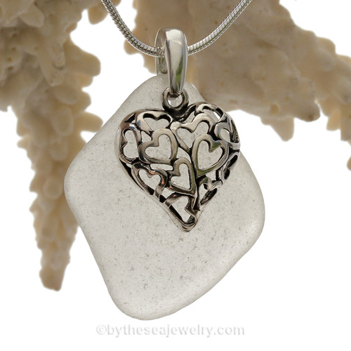 A  perfect piece of larger pure white  genuine sea glass with a solid sterling bail and detailed heart in hearts charm.