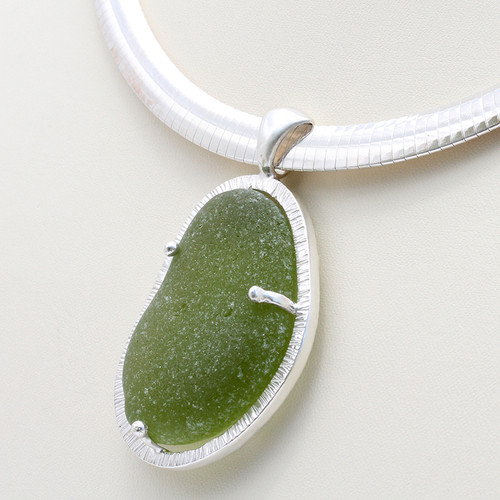 A huge piece of olive green sea glass from England set in a custom made cage. The sea glass is held secure front and back with soldered prongs.   Picture on 10MM Omega Necklace (INCLUDED - a $140 value).