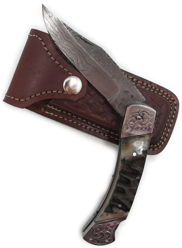"""Damascus Folder with Ram Horn Handle. 9"""" overall. 4"""" clip point damascus blade. Ram horn handle with decorative silver bolsters. Includes brown leather sheath."""