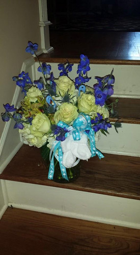 New Baby Celebration!!! White Hydrangeas, Roses, Delphinum with Ribbons and Pair of Socks. Girls Version is White Hydrangeas, Pink Roses, Larkspur or Snapdragons with Pair of Socks and Pink Ribbons.
