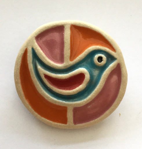 Bird brooch made from a white stoneware clay and coloured glazes. Supplied on a product card.