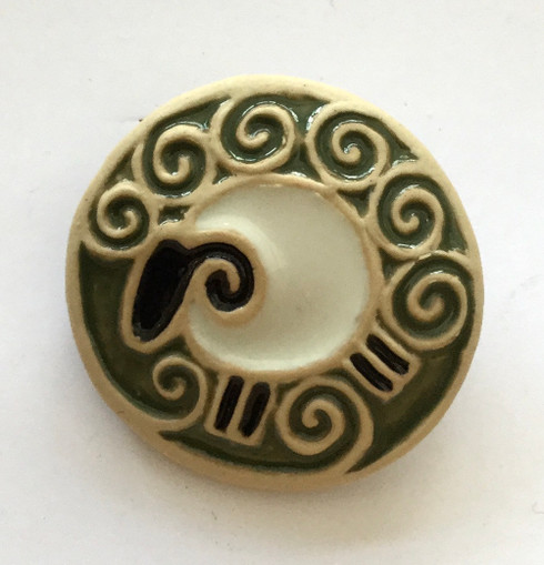 Sheep brooch made from a white stoneware clay and coloured glazes. Supplied on a product card.