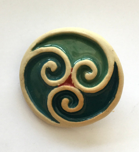 Triscele brooch made from white stoneware clay and coloured glazes.