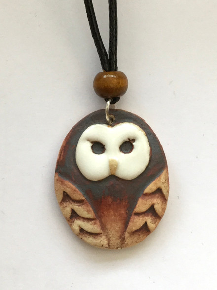 """Owl pendant made from a white stoneware clay and finished with glaze and oxide. The pendant is on an 18"""" black waxed cord choker with lobster clasp and extension chain. Supplied on a product card."""