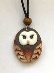 "Owl pendant made from a white stoneware clay and finished with glaze and oxide. The pendant is on an 18"" black waxed cord choker with lobster clasp and extension chain. Supplied on a product card."