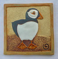 Puffin Plaque made from a textured stoneware clay and finished with glazes and metallic oxide. Metal hanger attached to back for hanging. Comes boxed.