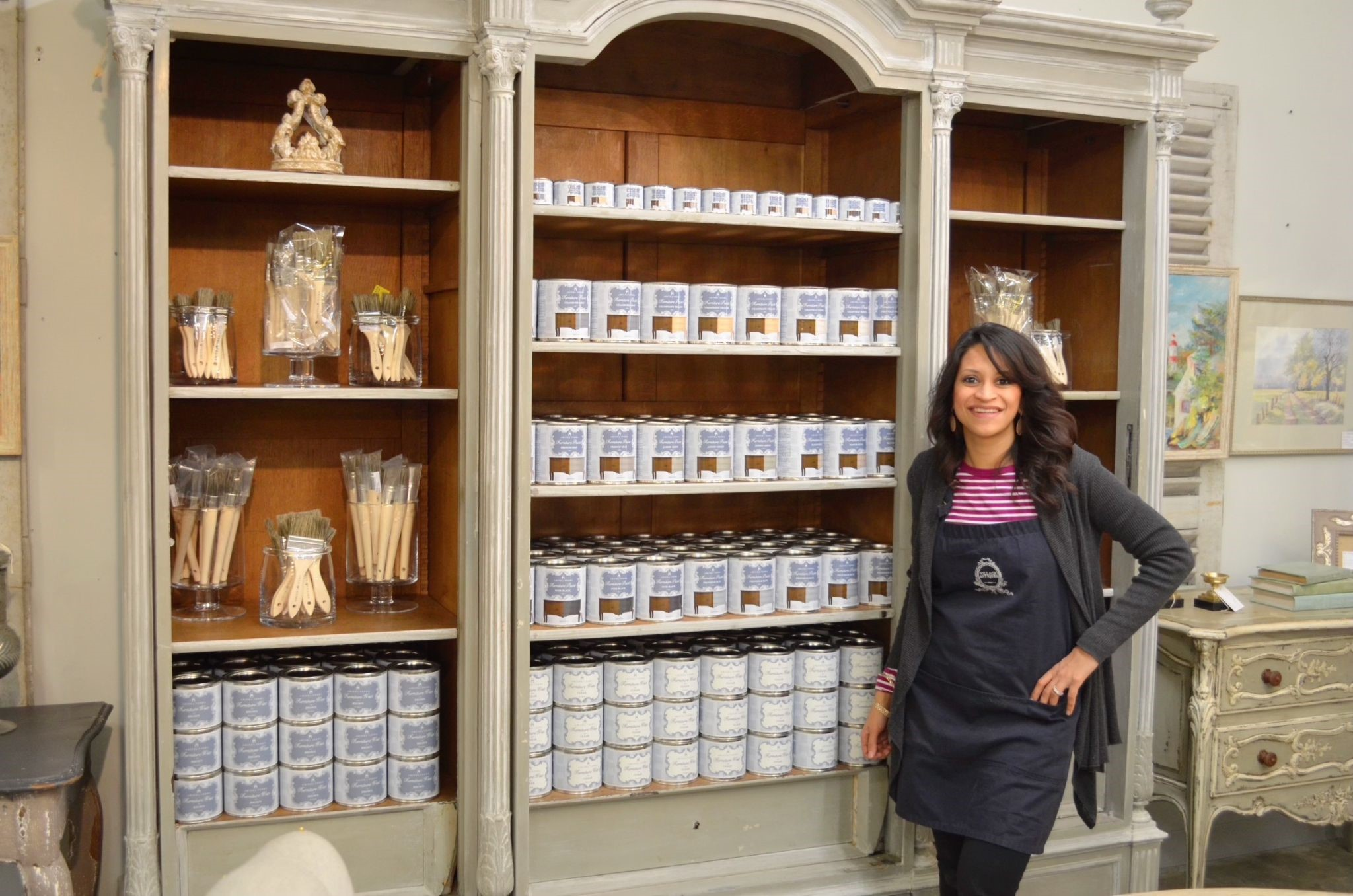 Amitha standing next to her fresh display of chalk finish paint that she designed herself, in her antique store in Houston, Village Antiques.
