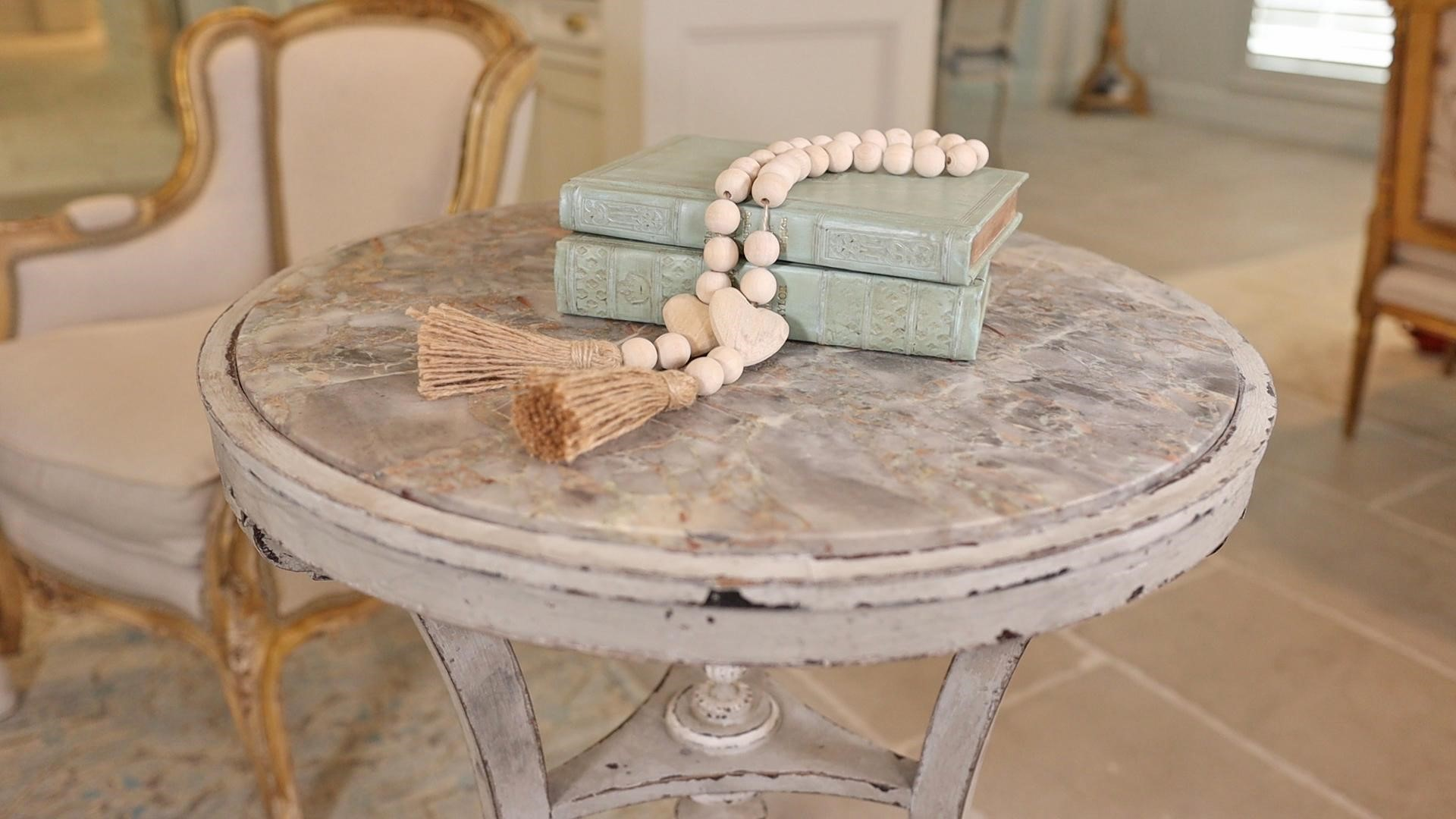 Mint blue vintage books with large wooden rosary-style beads on a distressed end antique table