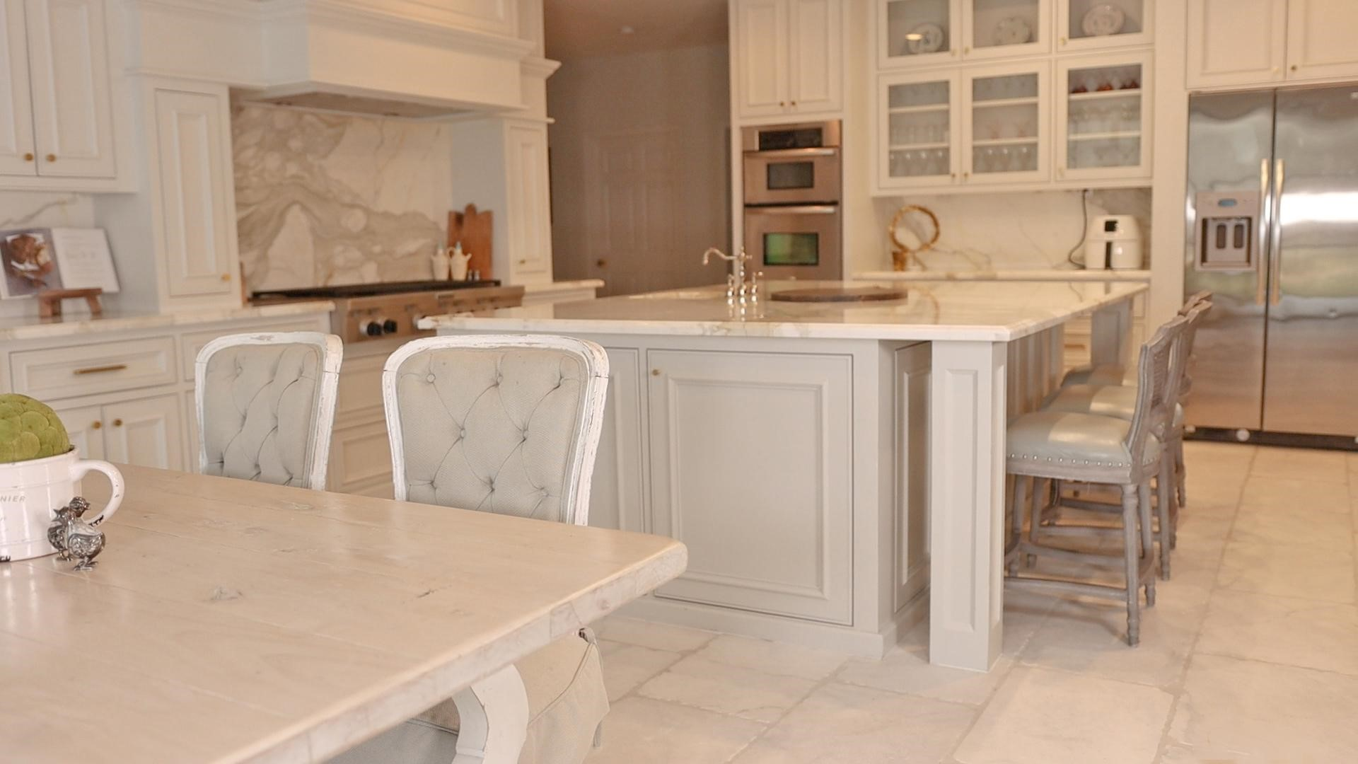 A view of white and gray farmhouse style kitchen with breakfast nook and kitchen counter seating
