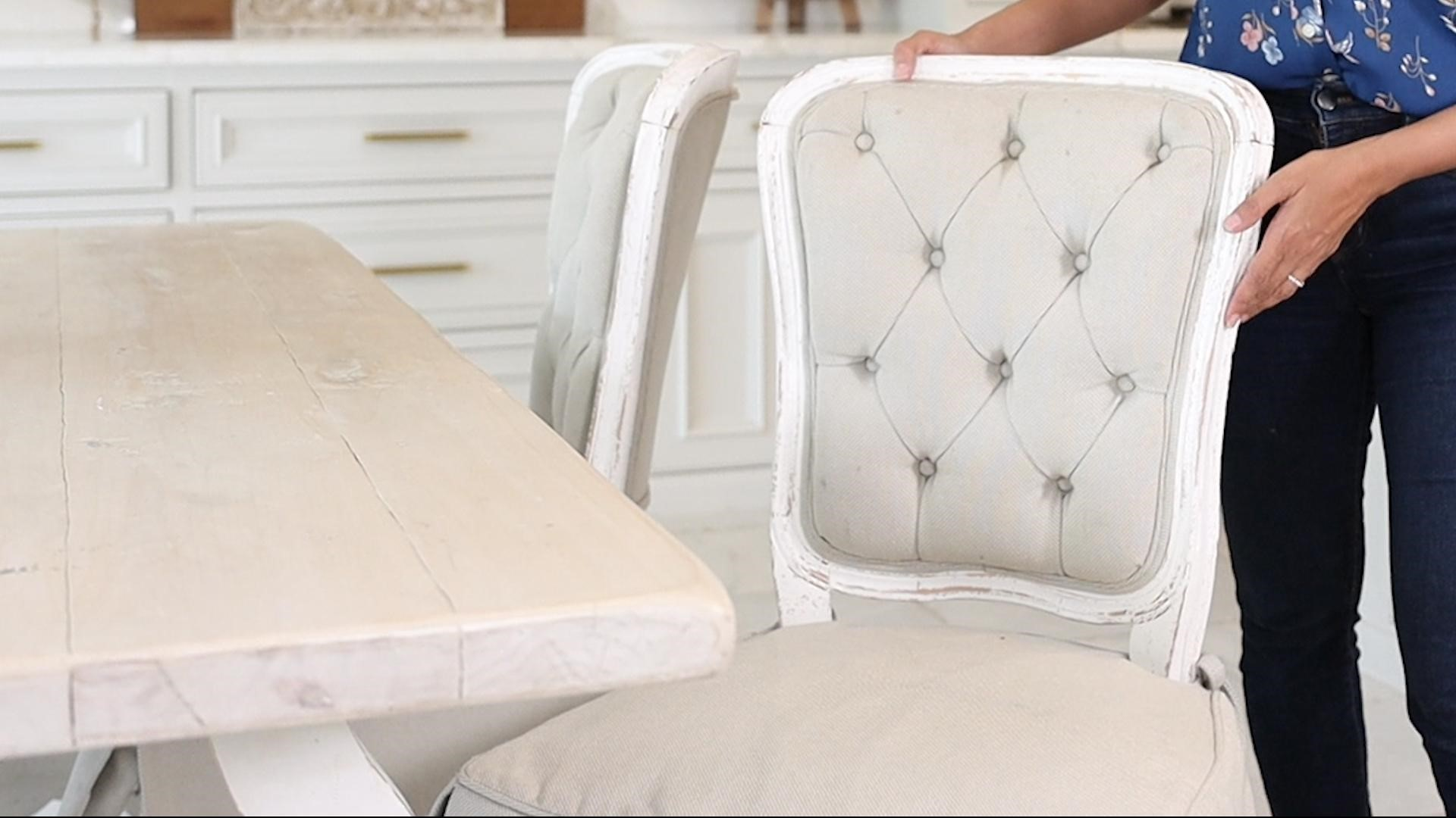 Pulling out the tufted curved, distressed wood chairs at the breakfast nook