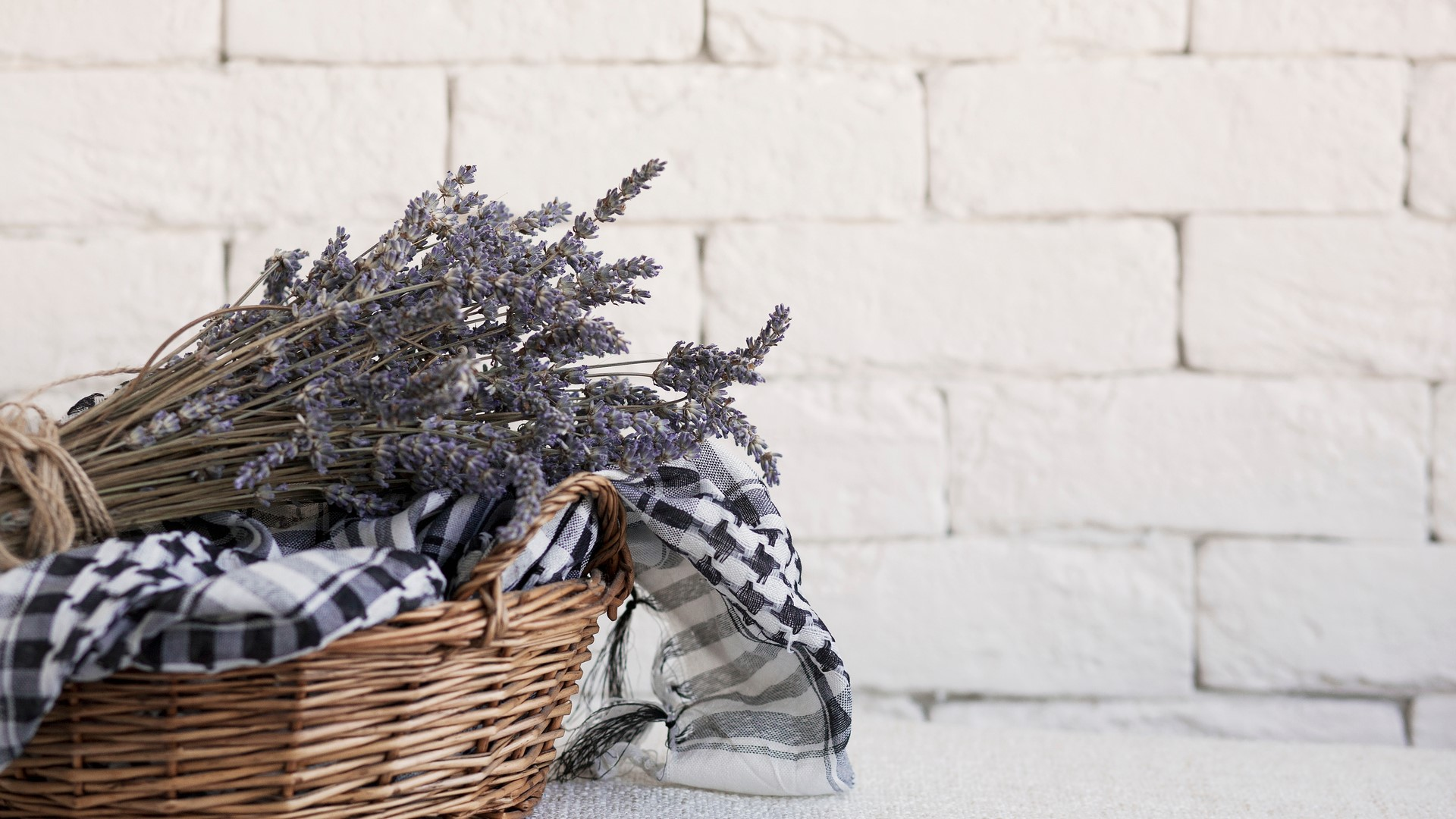 A wicker basket against a white-bricked wall filled with navy blue and white gingham napkins and a bundle of dried lavender sitting on the countertop of a country cottage-style home against a slaked whitewashed brick wall.