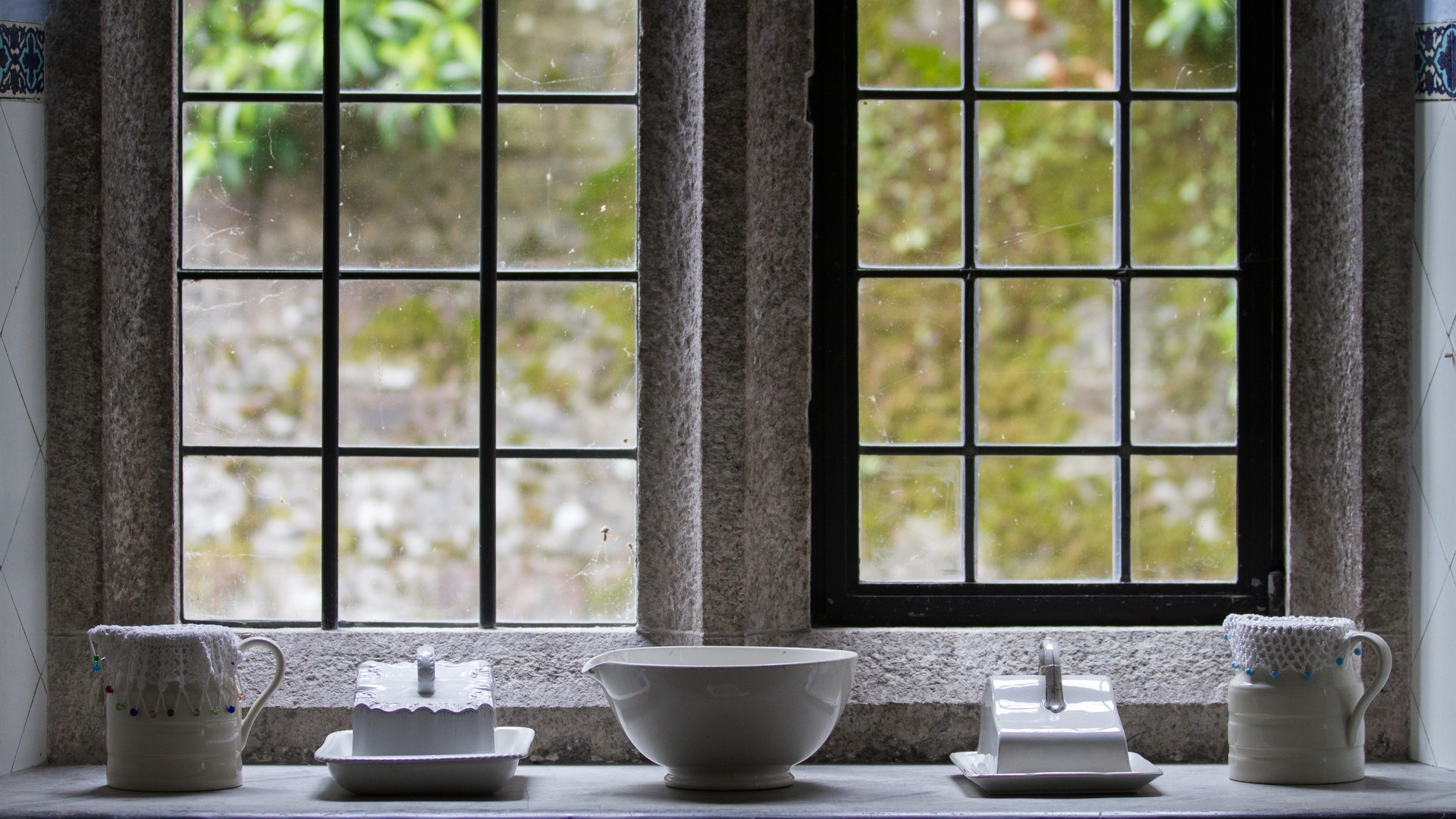 A display of French cottage kitchenware to dress up a black steel frame windowsill.