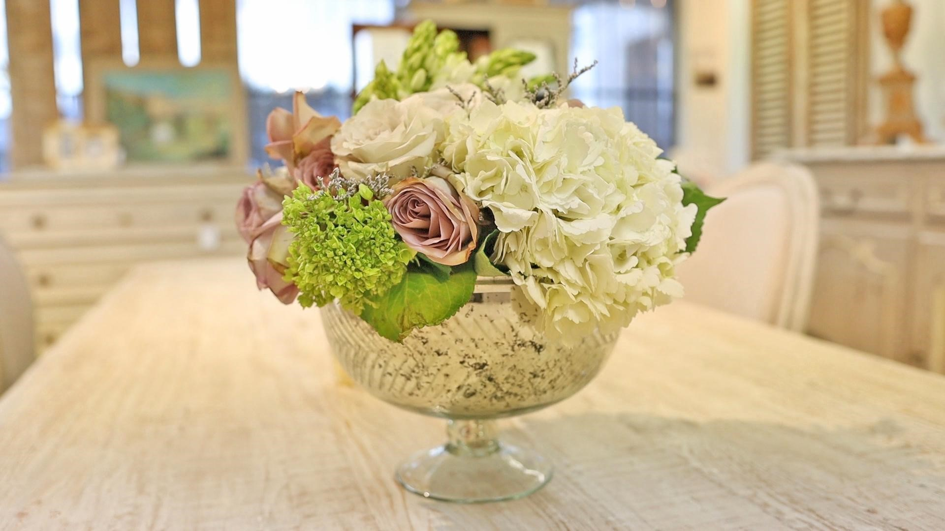 Floral bowl arrangement in silver rustic bowl with white hydrangeas, pink roses, and green hydrangeas on farmhouse style table