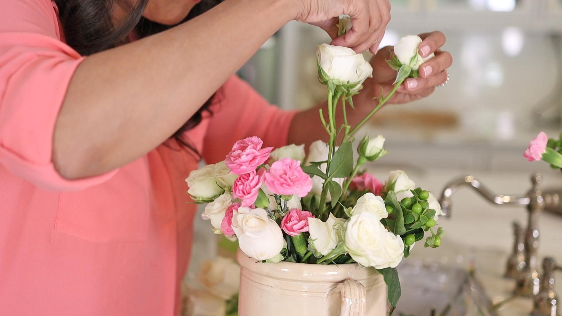 Amitha placing white roses and pink flowers in a french country confit pot vase.