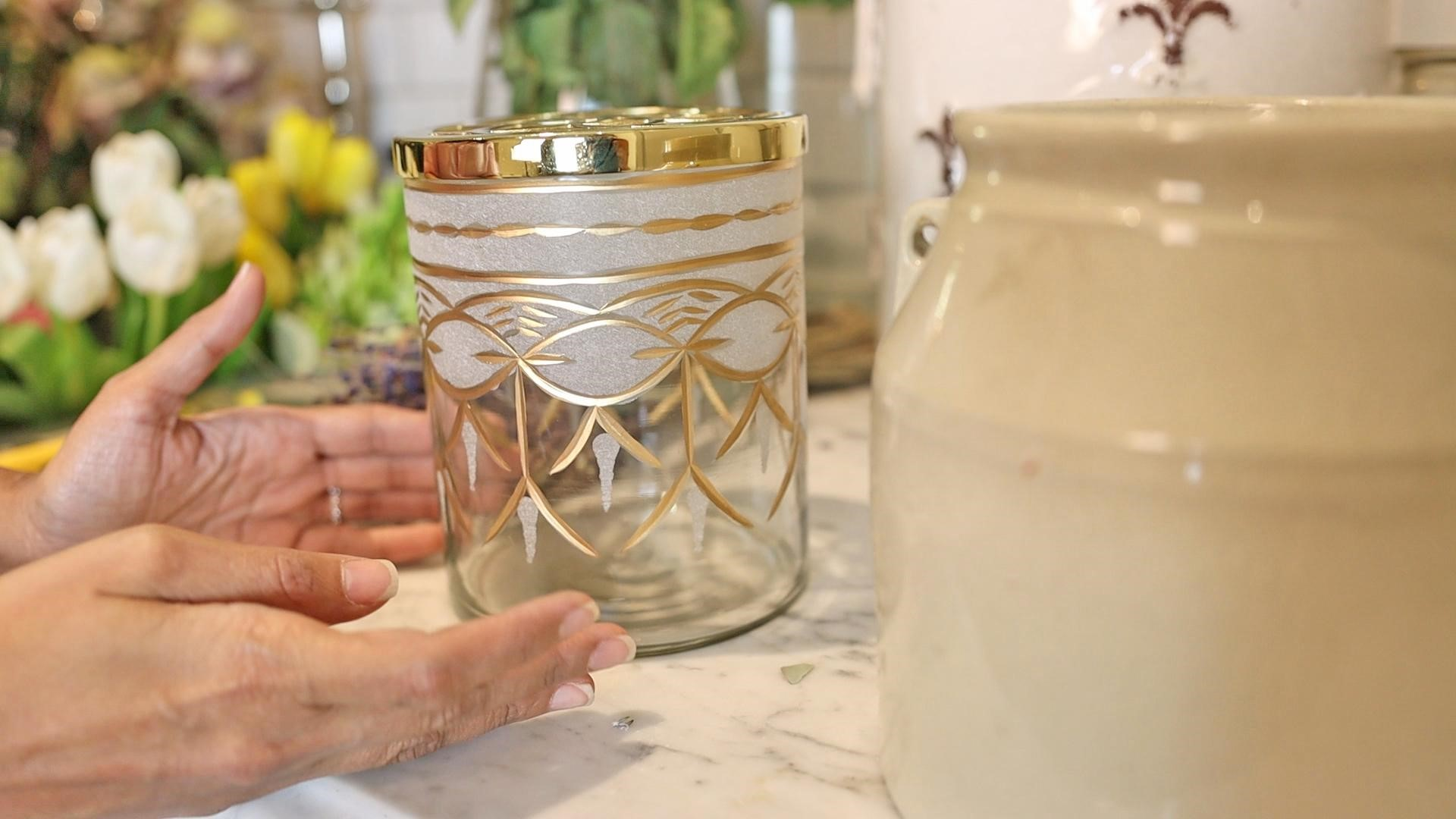 Amitha pointing to medium etched glass cylindrical vase with gold detail and frog flower base
