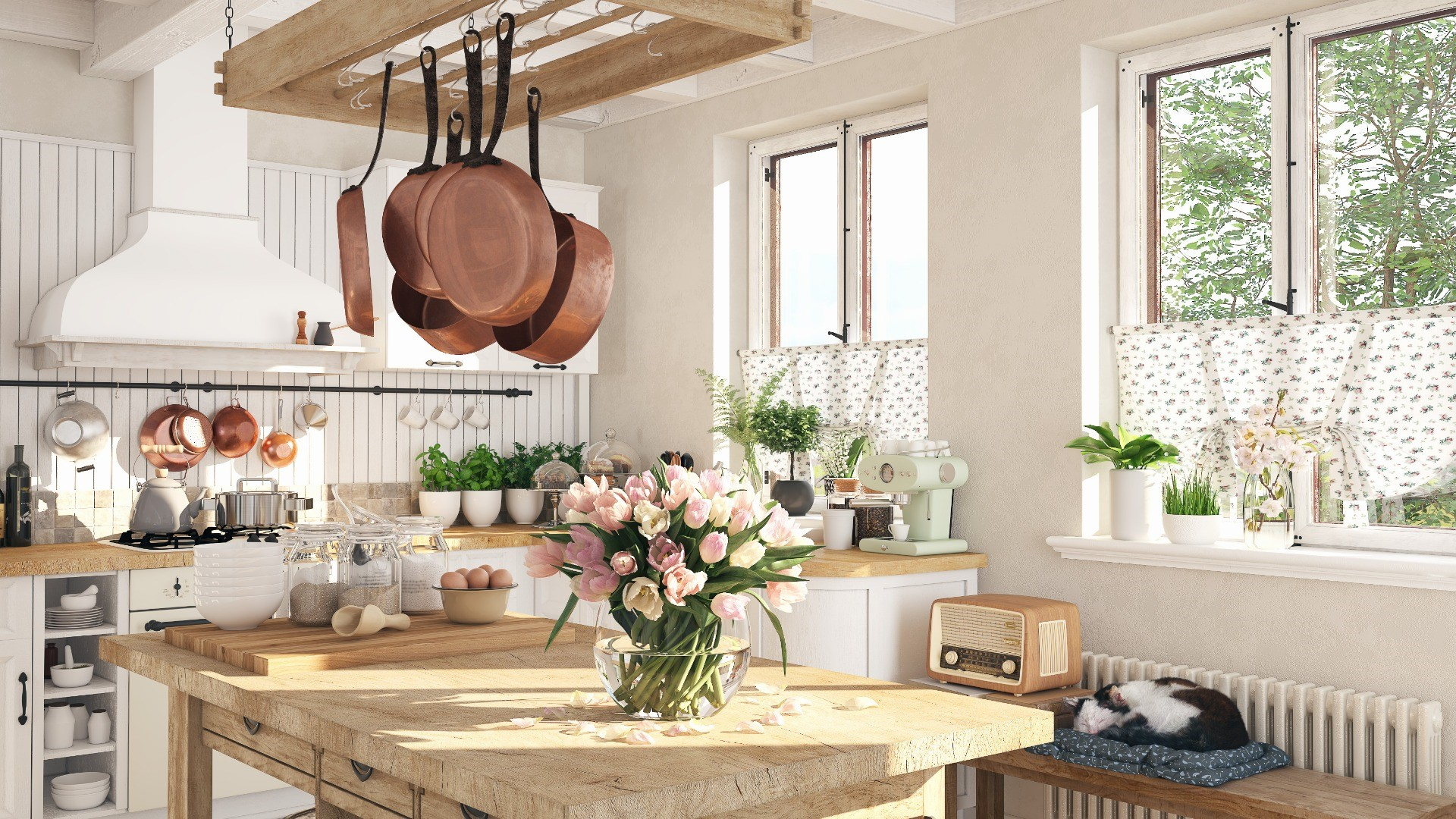 Bright and airy French cottage style kitchen with large wooden island styled with floral arrangements, creamware, linen tablecloths, simple white cabinets and a copper pot rack.