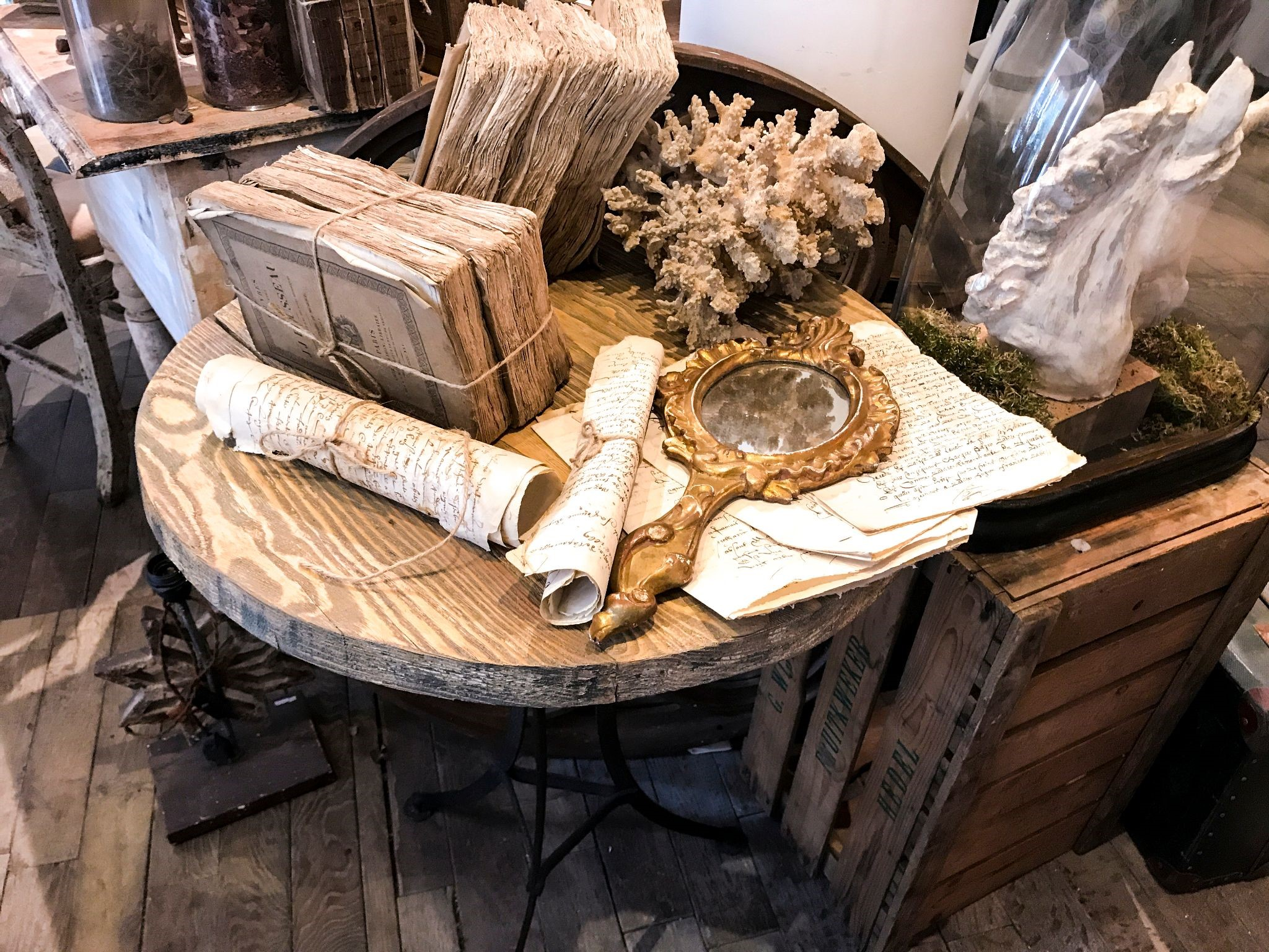 Natural colored wooden table surrounded by antique books, aged mirrors, dried florals, and ceramic decor.