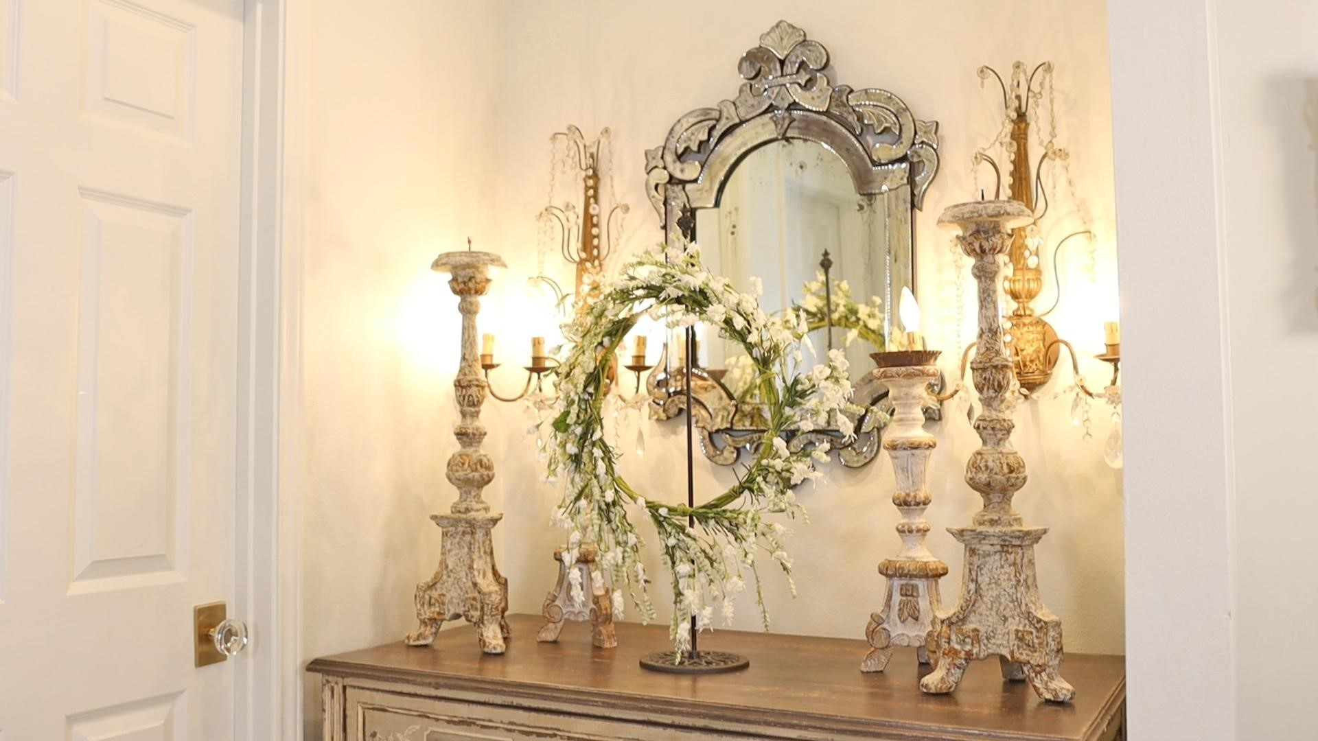 How Amitha styles her hallway with French country decor including gilt and crystal sconces, etched Venetian style glass mirror, distressed chalk painted chippy white and gold candle holders atop a chest of drawers.