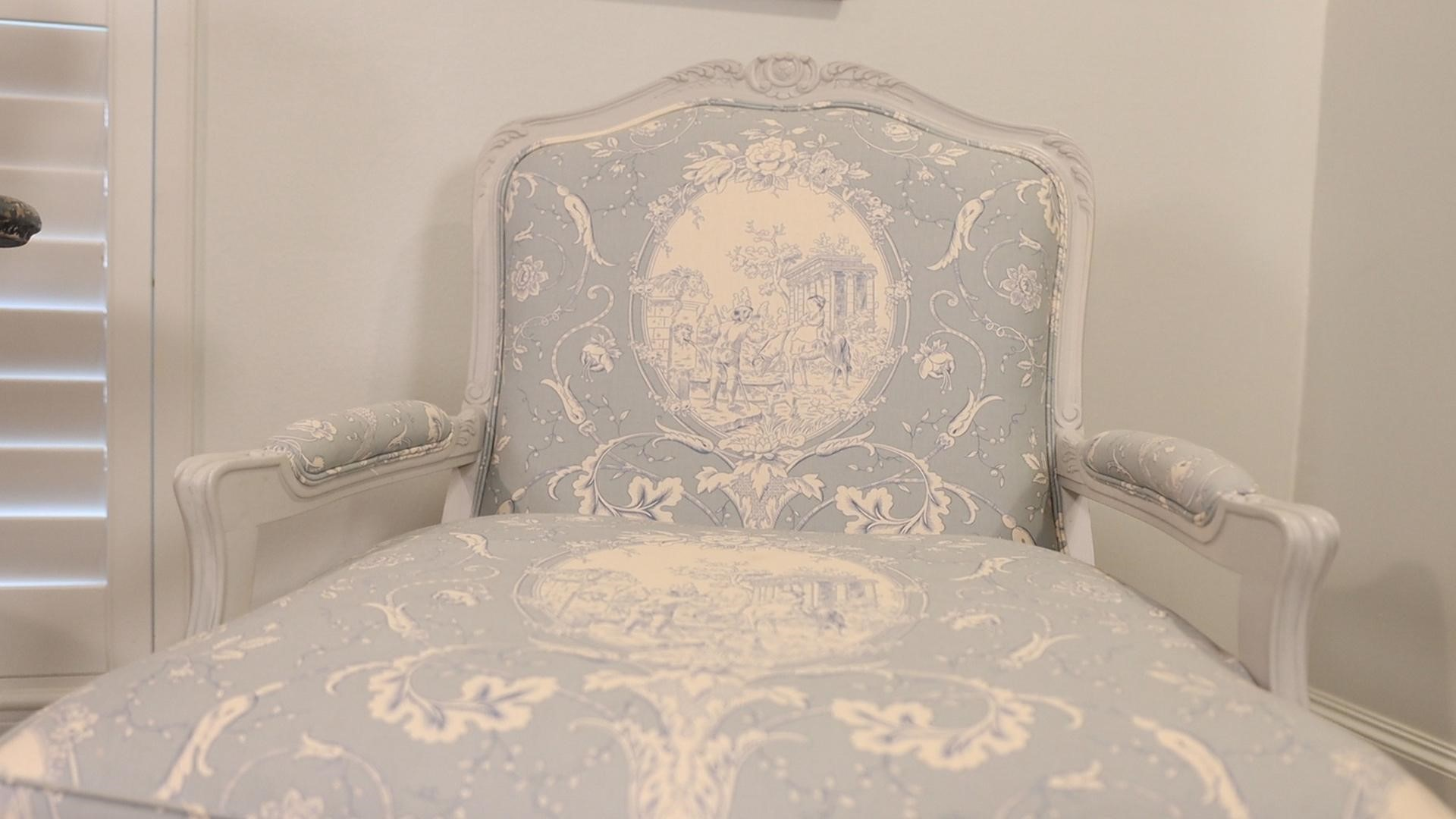 A close-up of the French country furniture armchair in blue with cream pattern details, by Amitha