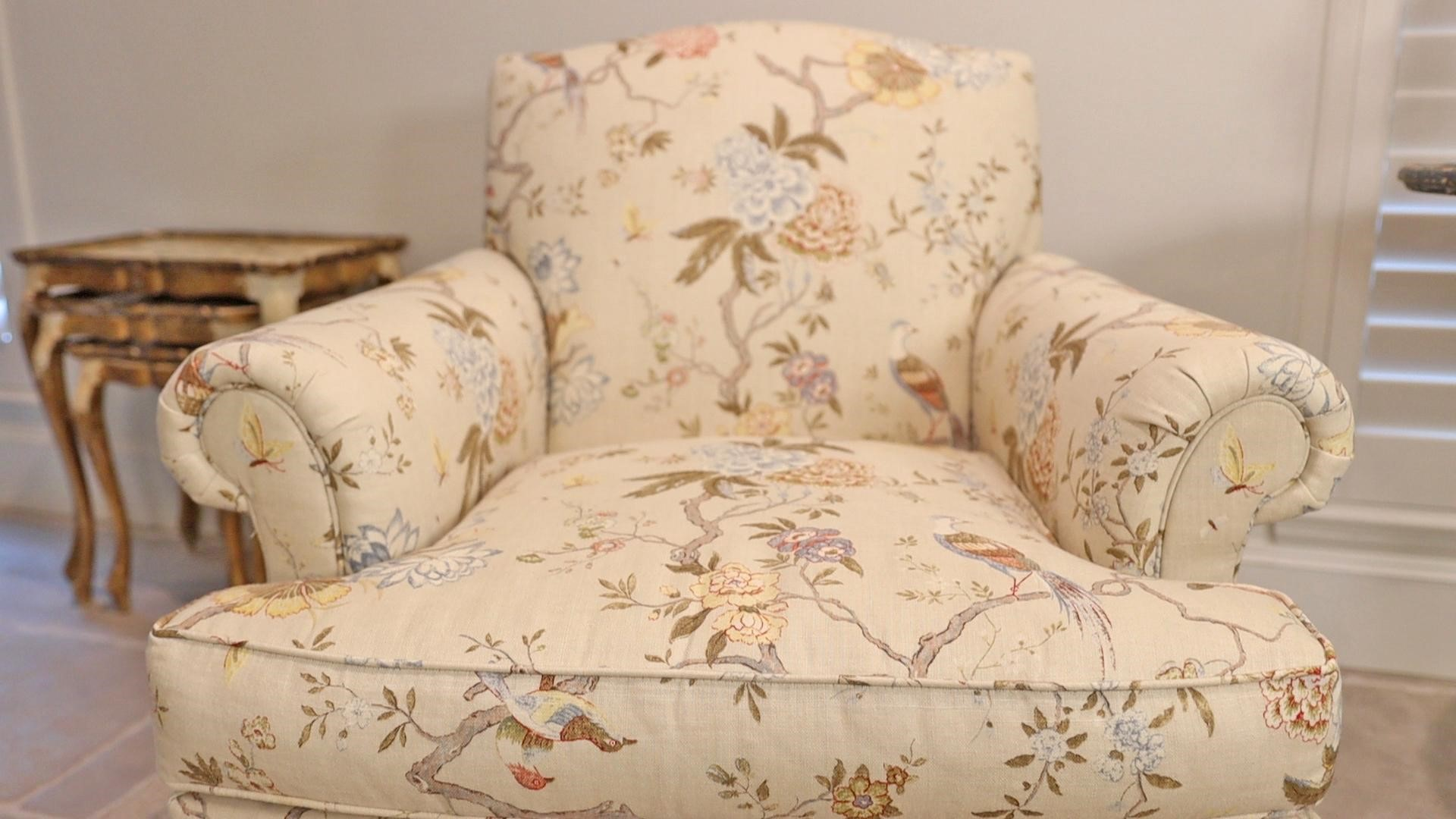 A close-up of the French country furniture armchair in cream with hydrangeas, birds, butterflies, and floral details, by Amitha.
