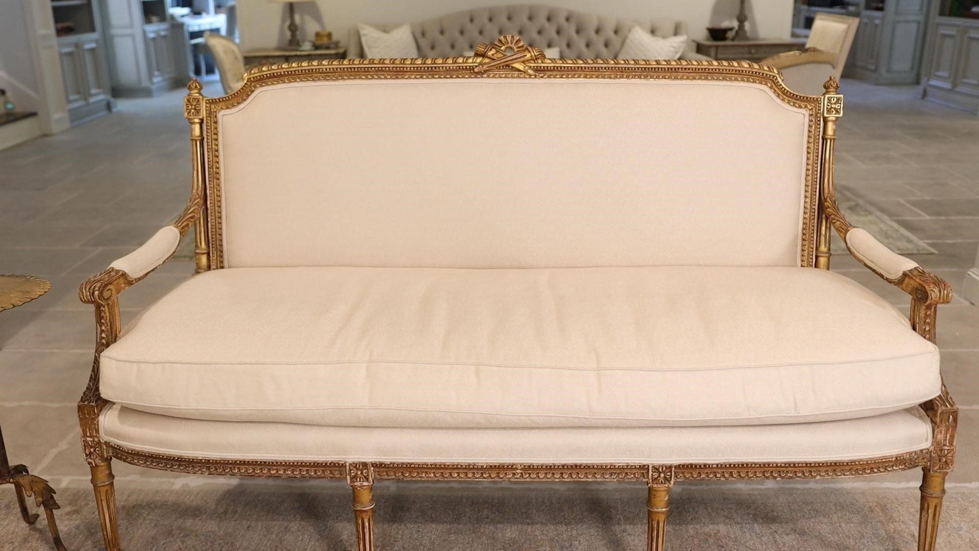 French country furniture settee with cream fabric and gold-gilt trim and carved details, by Amitha